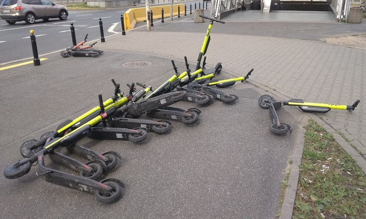 E-scooters lying on a sidewalk.